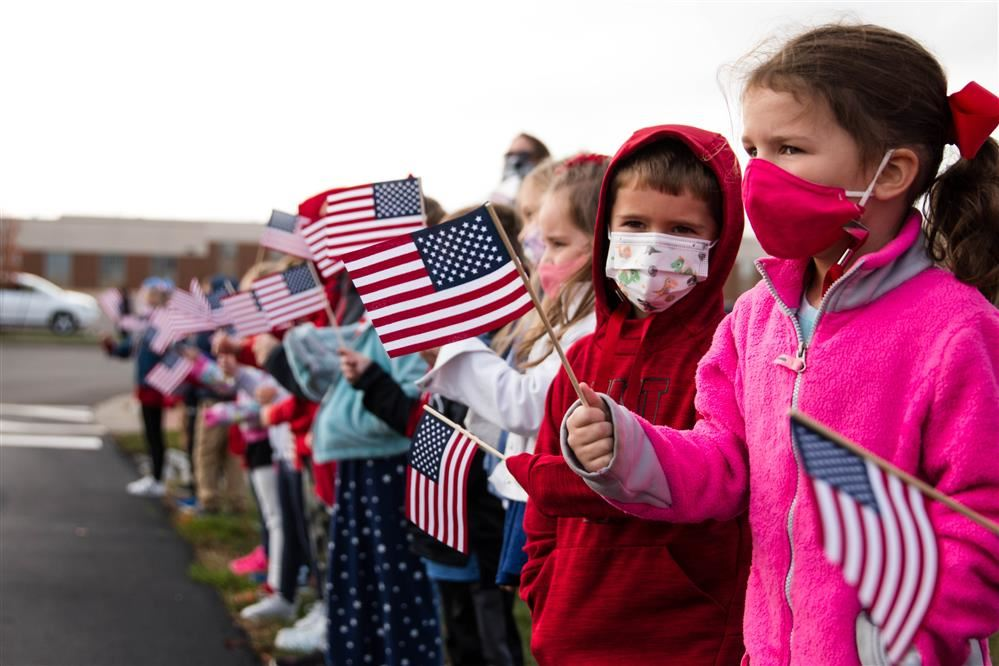 Students of Center Grove Elementary wave flags and show off their signs during their Veterans Day c